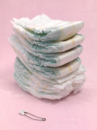 A stack of modern disposable nappies isolated against a pink background Stock Photo - 7513611