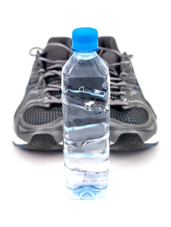 A bottle of water and joggers isolated against a white background photo