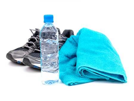 A bottle of water, joggers and a sports towel isolated against a white background photo