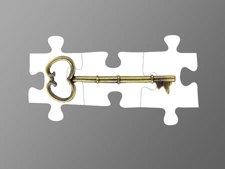 Jigsaw puzzle pieces of a key isolated against a grey background photo