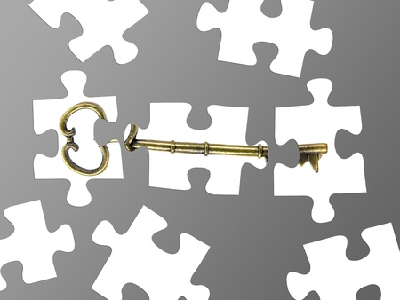 Jigsaw puzzle pieces of a key isolated against a grey background Stock Photo - 8446320