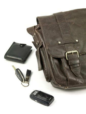 A leather bag and contents isolated against a white background photo