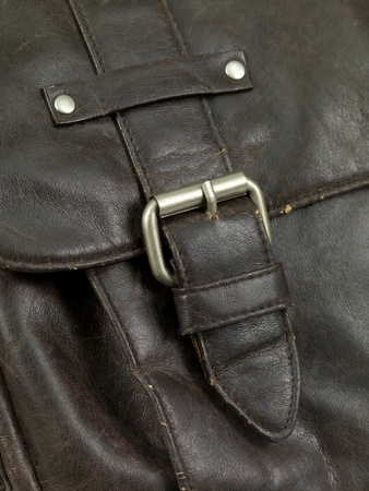 A close up shot of a leather bag buckle photo