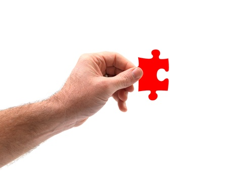 A hand holding a jigsaw piece isolated against a white background Stock Photo