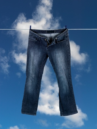 red jeans: Clothes on a clothes line isolated against a blue sky Stock Photo