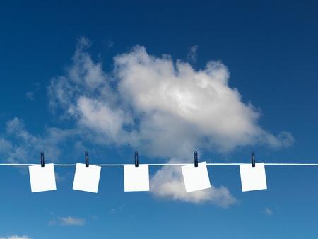 Post it Notizen auf einer Wäscheleine vor einem blauen Himmel isoliert