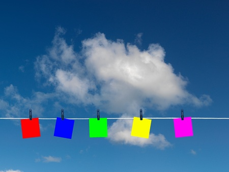 Post it notes on a clothes line isolated against a blue sky photo