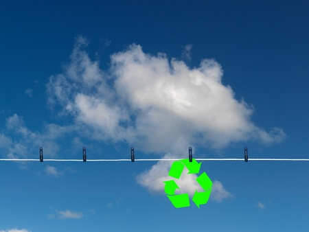 A recycle symbol on a clothes line isolated against a blue sky photo