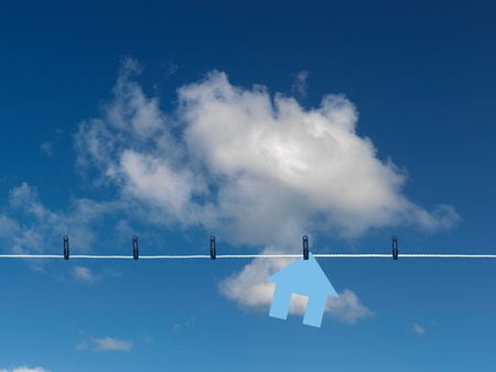 A home symbol on a clothes line isolated against a blue sky Stock Photo