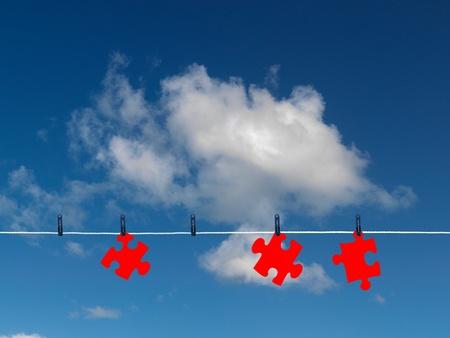 Jigsaw pieces on a clothes line isolated against a blue sky photo