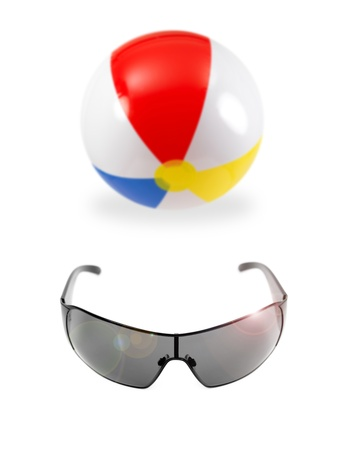 A beach ball and sunglasses isolated against a white background photo