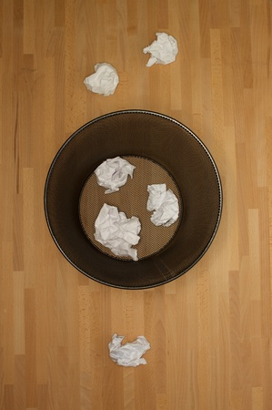 A trash bin isolated on a wooden floor photo