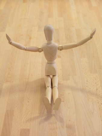 A wooden manikin isolated on a wooden floor photo