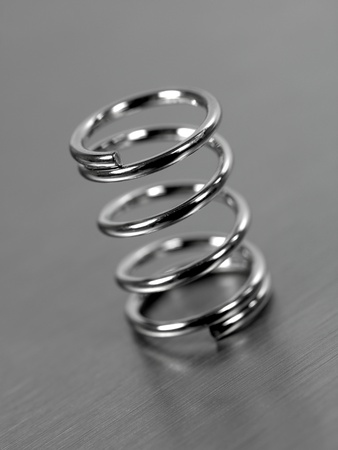annealed: A spring isolated against a silver  background Stock Photo