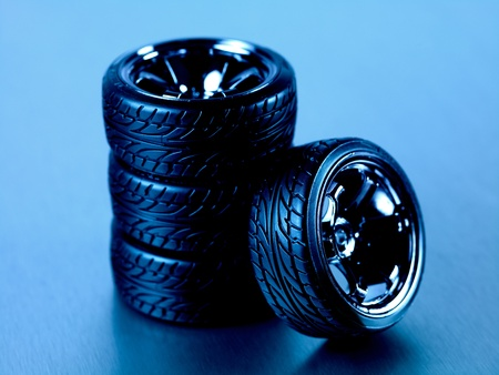 Rubber tyres with sports rims on a silver background Stock Photo - 10486082