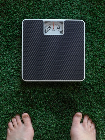 Bathroom scales isolated against green grass photo