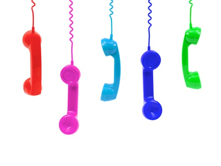 Colored telephone handsets isolated against a white background