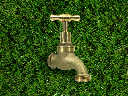 A tap isolated on artificle green grass photo