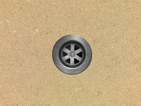 A drain hole isolate on a sandy beach photo
