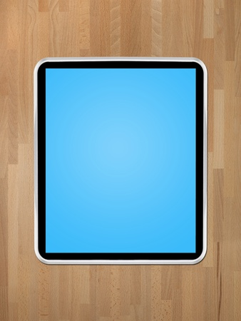 A computer tablet isolated against a wooden background Stock Photo - 12388727