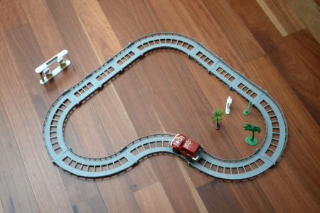 slot car track: A toy race track on a wooden floor
