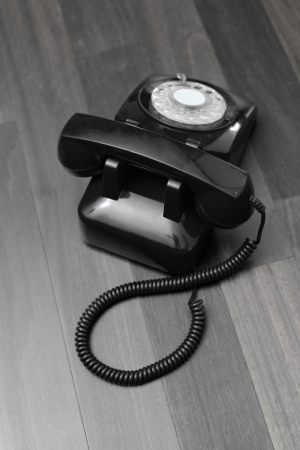 A vintage telephone isolated on a wooden floor photo