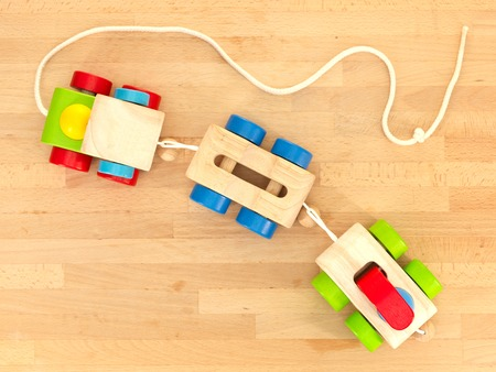 babyroom: A close up shot of toys scattered over a wooden floor