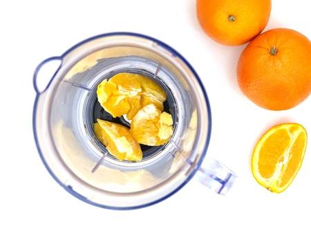 liquidiser: A close up photo of a juicer blender and oranges