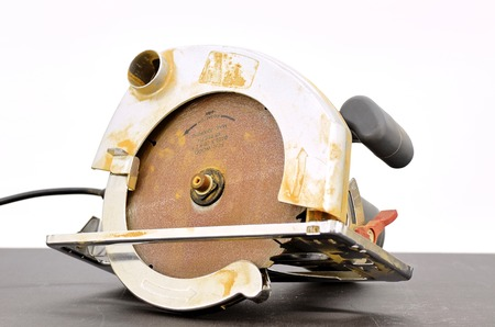 boilersuit: A studio photo of a industrial circular saw