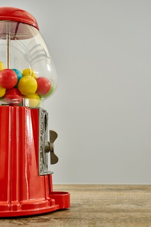 A studio photo of a vintage gum ball machine