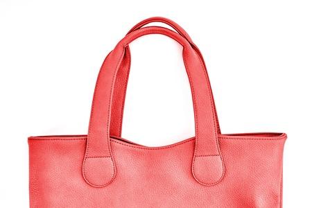 A studio photo of a ladies red handbag