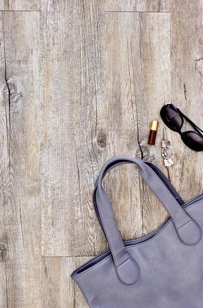A studio photo of a ladies grey handbag
