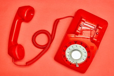 A studio photo of a red rotary telephone Stock Photo