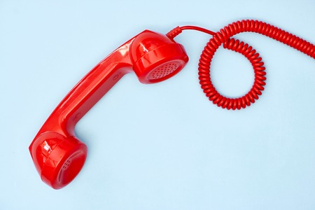 A studio photo of a red rotary telephone Stockfoto