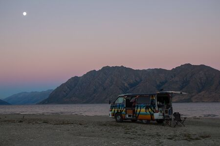 Freedom camping with campervan in front of lake hawea with mountains in the background in new zealand south island
