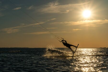 kitesurfer doing unhooked backroll in sunset with sunstar and beautiful silhouette
