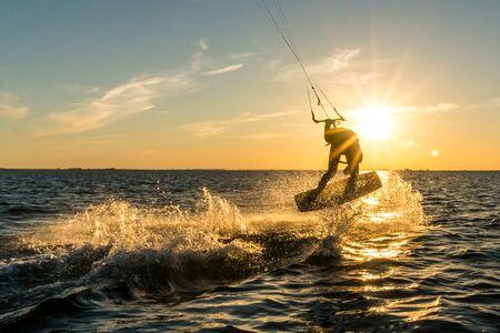 kitesurfer doing tricks in sunset Stock Photo
