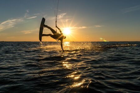 kitesurfer doing handslide in sunset with sunstar and beautiful silhouette Stock fotó