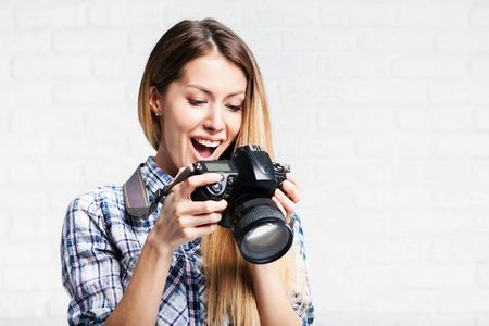 Mujer fotógrafo toma imágenes con la cámara réflex digital Foto de archivo - 67465551
