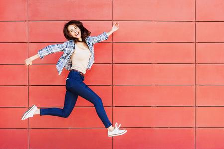 빨간색 벽에 점프 즐거운 행복 젊은 여자 스톡 콘텐츠
