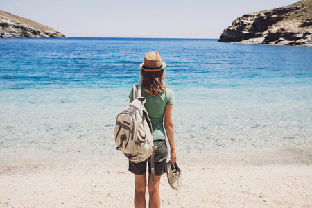 Female traveler looking at the sea, travel and active lifestyle concept