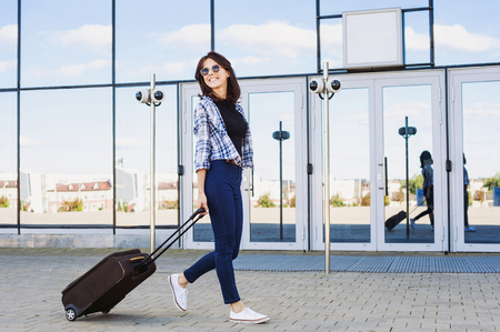 Young woman walking with luggage suitcase, vacations, travel and active lifestyle concept Stock Photo