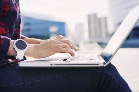 Young woman wearing smart watch using laptop computer. Female hands working on laptop outdoor