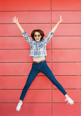 Joyful happy young woman jumping against red wall. Excited beautiful girl portrait