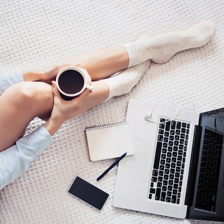 Young woman drinking coffee and using laptop at home Stock Photo