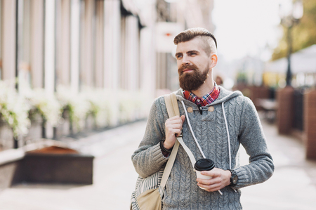 Cheerful young man wearing warm clothes walking outdoors