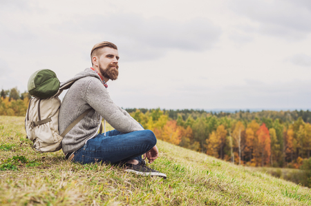 若い男旅行者の丘、旅行やアクティブなライフ スタイル コンセプトの上に座っています。