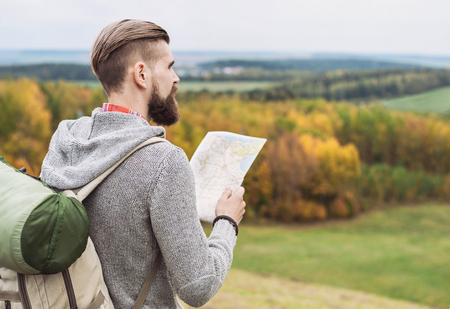 Young man traveler standing on top of the hill and looking to the map. Travel and active lifestyle concept Stock Photo
