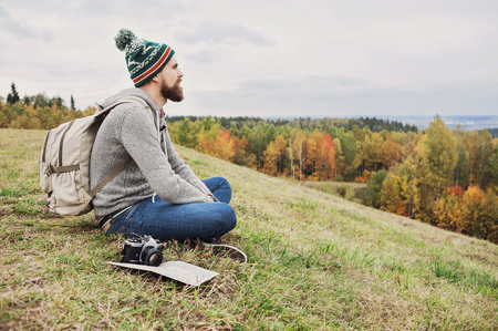Young man traveler sitting on top of the hill. Travel and active lifestyle concept