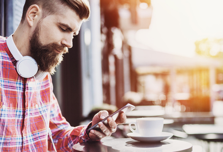 Close up portrait of young man using smartphone in a cafe outdoors